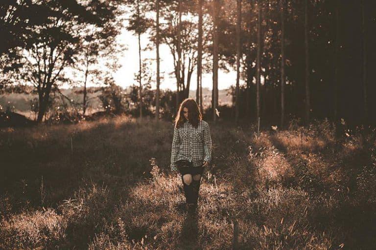 Ein einsames Mädchen geht durch den Wald