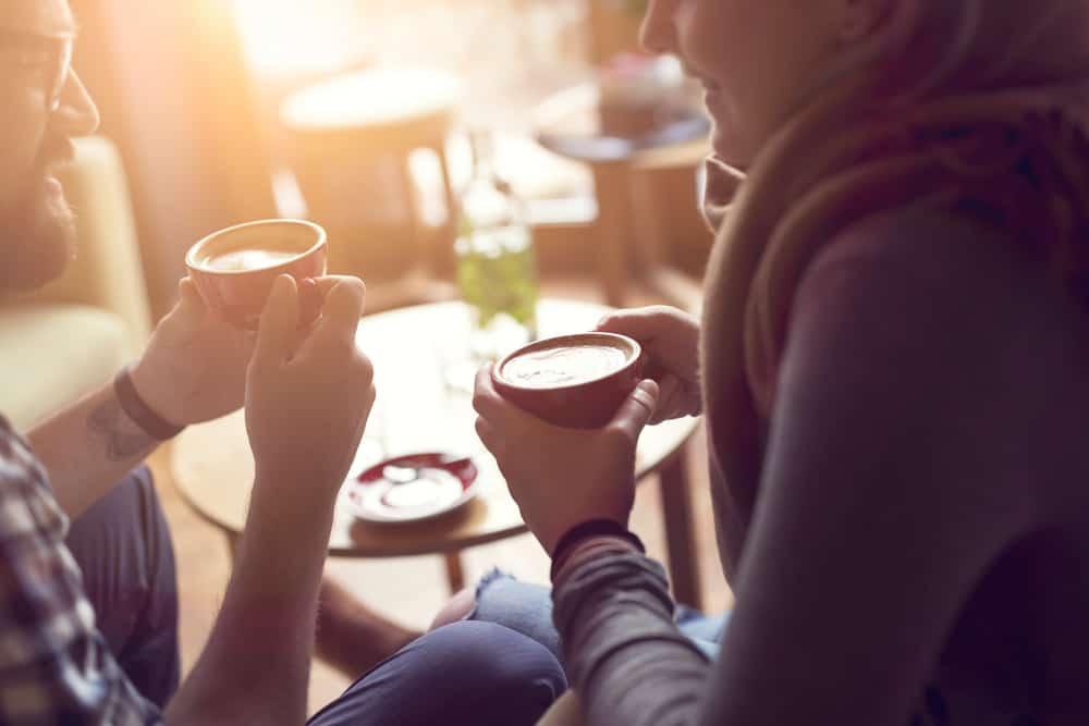Ein junges Paar sitzt in einem Café und trinkt Kaffee