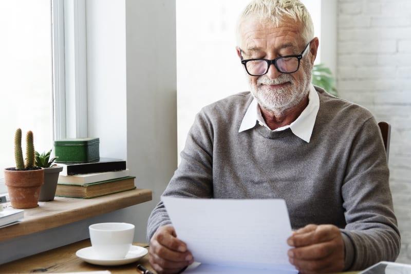 Ein lächelnder alter Mann mit Brille liest einen Brief