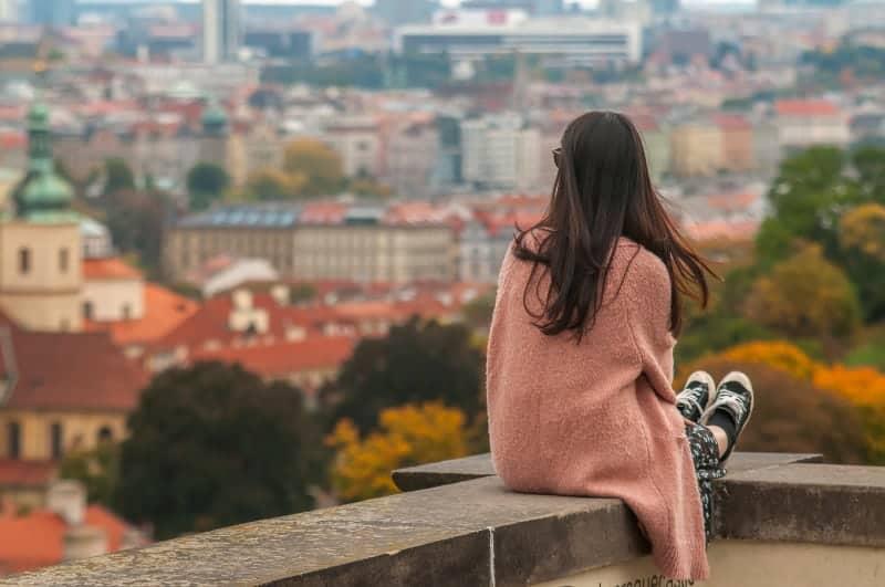Eine Frau sitzt auf einem Betonzaun und beobachtet eine Stadt