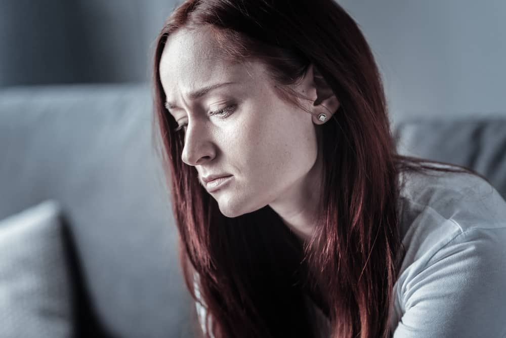 Eine schöne Frau mit einem traurigen Blick sitzt im Raum