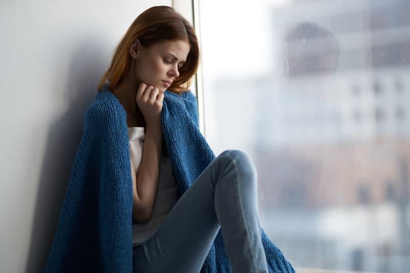Eine traurige Frau in einer Decke steht am Fenster