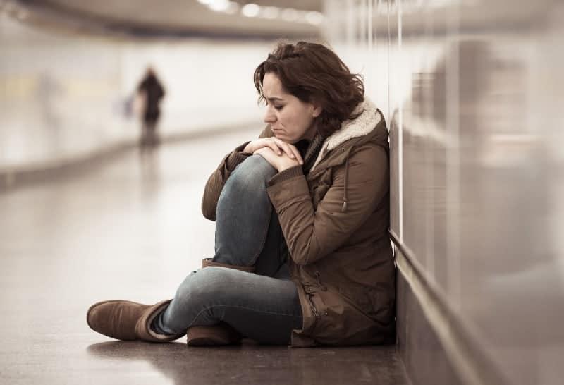 Eine traurige Frau sitzt auf dem Boden