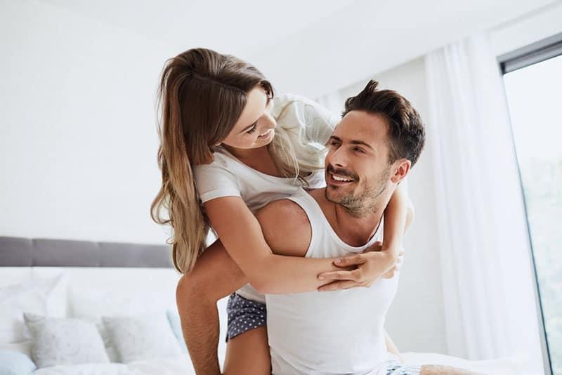 Frau, die Mann im Schlafzimmer umarmt