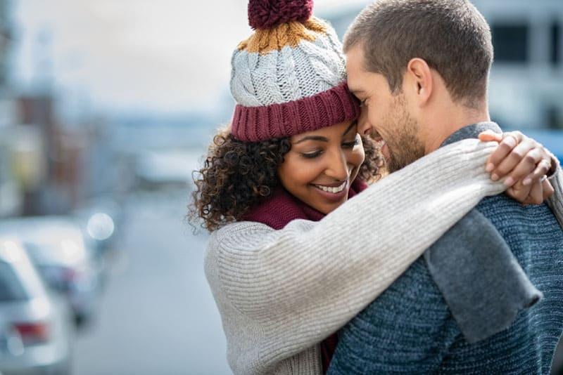 Frau mit Wintermütze umarmt Mann