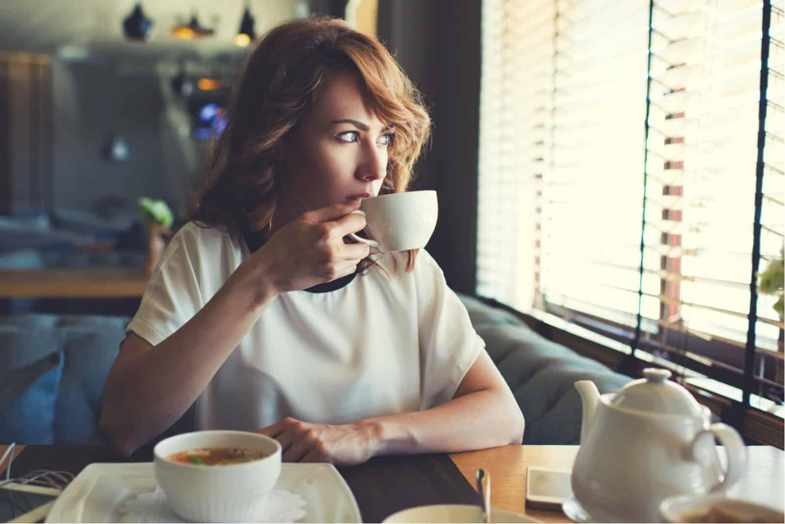 Frau sitzt im Café und trinkt Kaffee