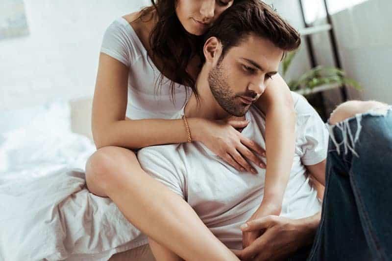 Frau umarmt besorgten Mann von hinten