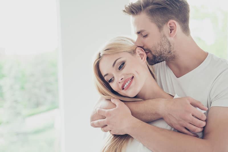 Mann küsst Frau in den Kopf