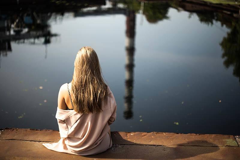 Rückansicht der blonden Frau, die auf hölzernem Dock vor See sitzt
