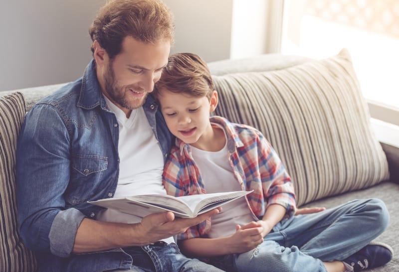 Vater und Sohn sitzen auf der Couch und lesen ein Buch