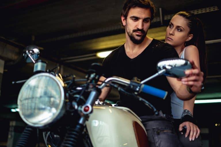 ein Mädchen, das mit einem Mann auf einem Motorrad sitzt