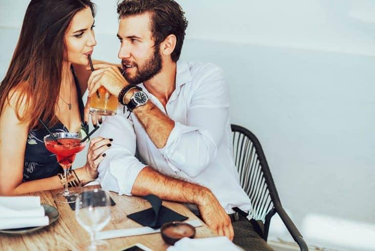 ein Mann, der einem Mädchen gibt, Saft mit einem Strohhalm zu trinken