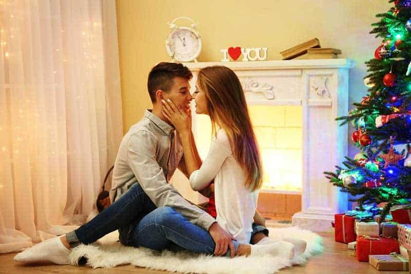 ein glückliches Liebespaar, das während der Weihnachtsferien auf dem Boden des Raumes sitzt und sich küsst