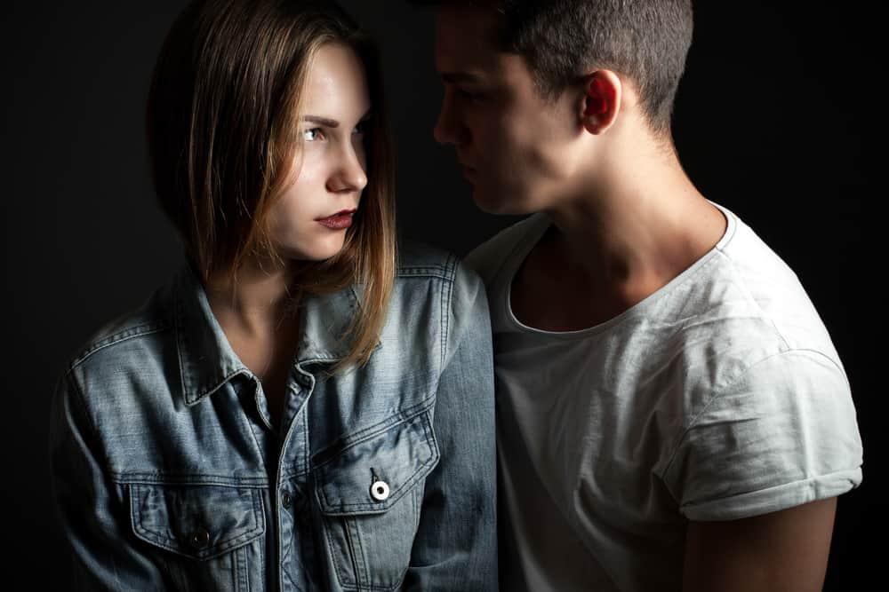 ein junges Paar, das im Dunkeln steht und sich ansieht