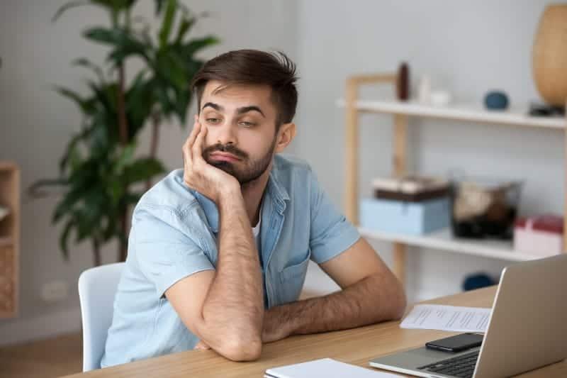 ein nachdenklicher Mann sitzt an seinem Schreibtisch