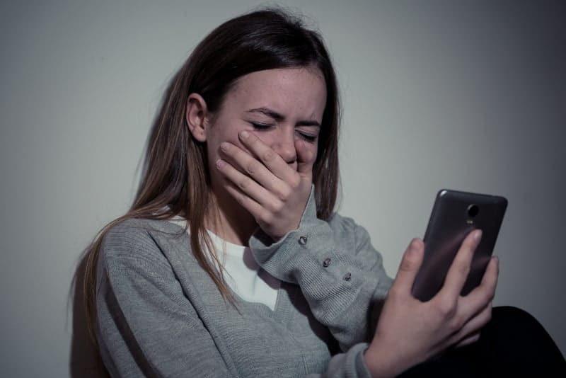 eine weinende Frau, die mit einem Handy in der Hand sitzt