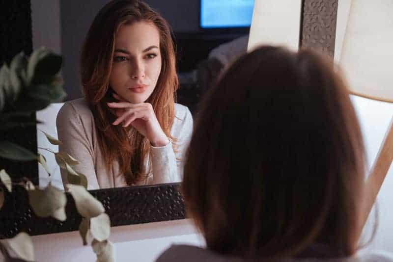 ernsthafte Frau, die sich im Spiegel schaut
