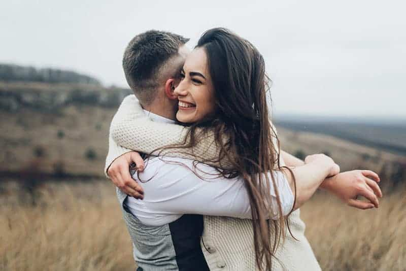 glückliche Frau, die Mann im Freien umarmt