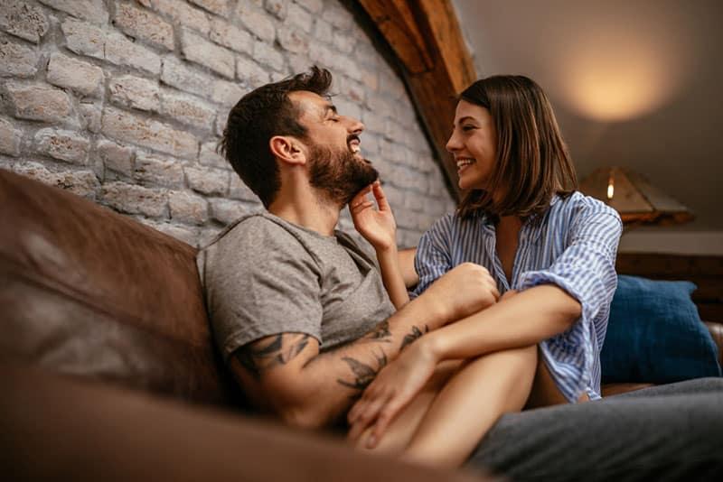 glückliche Frau, die auf Mann im Wohnzimmer sitzt