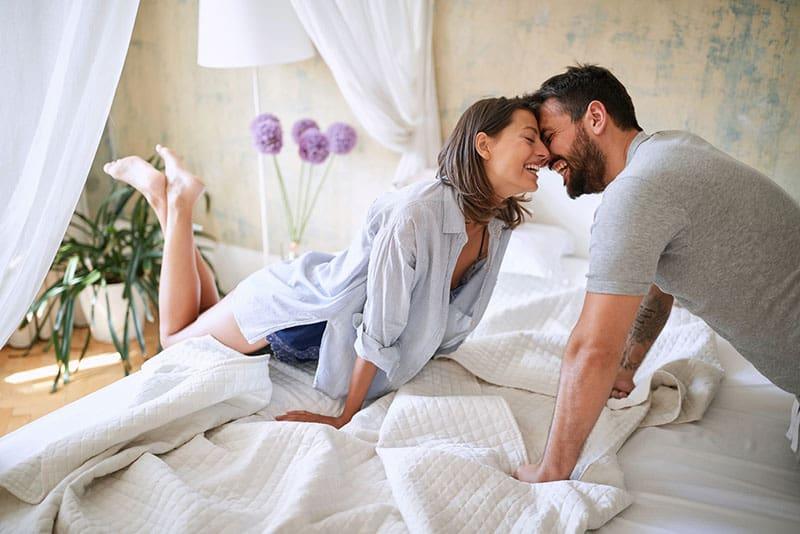 glückliches junges Paar, das im Schlafzimmer kuschelt