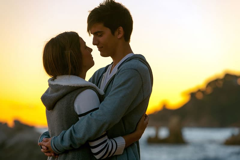 junges Paar, das bei Sonnenuntergang umarmt