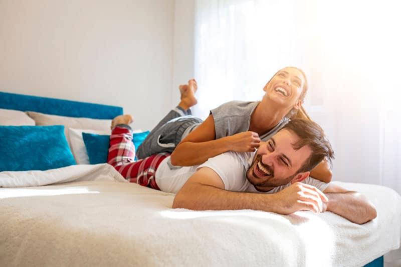 junges Paar spielt auf dem Bett und lacht