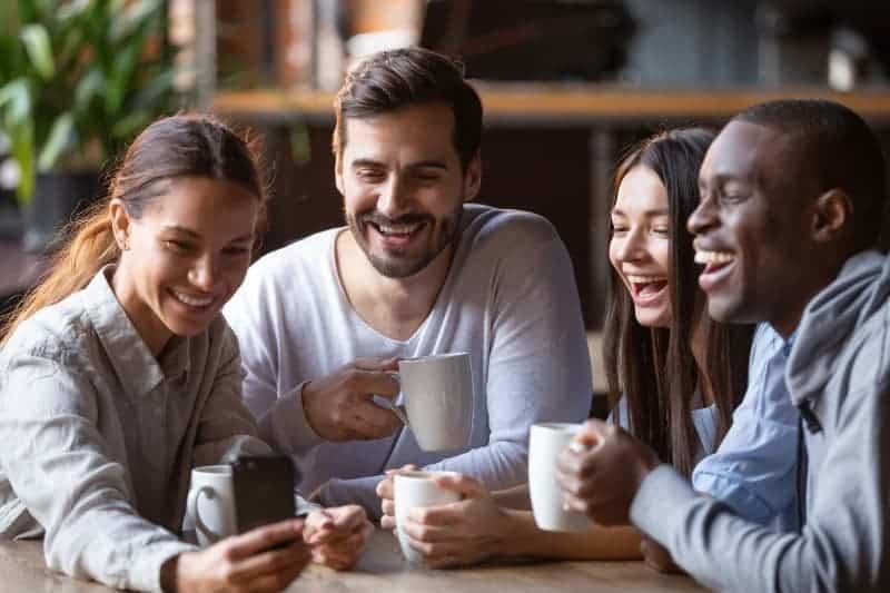 lächelnde Freunde beim Kaffee beobachten etwas auf ihren Handys