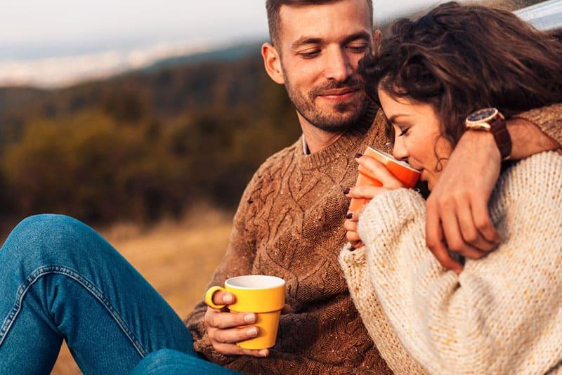 lächelnder Mann, der Frau betrachtet, die Saft trinkt