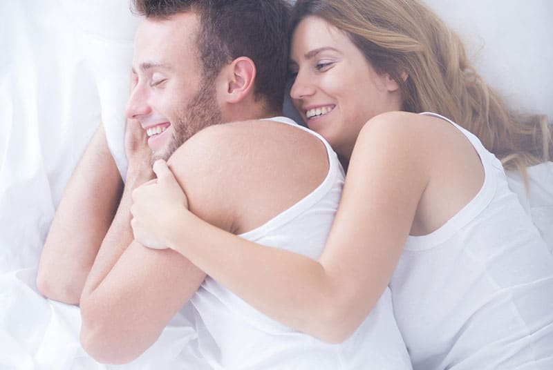 lächelndes Paar im Bett liegen