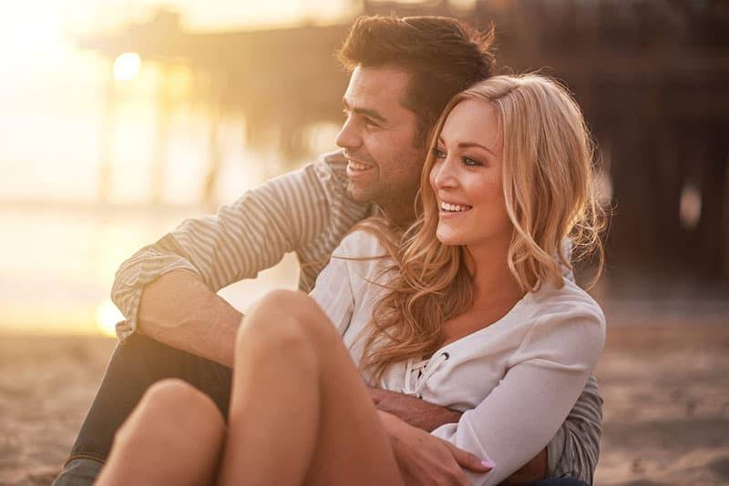 lächelndes Paar sitzt in Umarmung