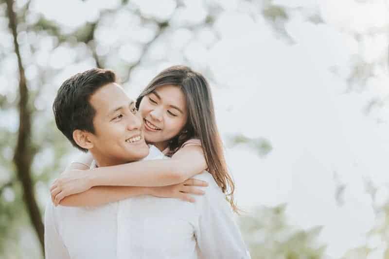 lächelndes Paar, das draußen umarmt