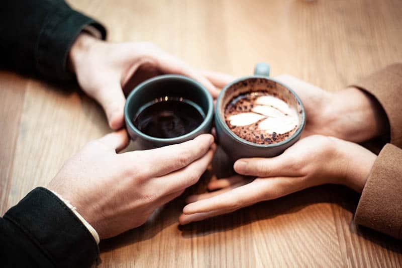 männliche und weibliche Hände halten zwei Tassen Kaffee auf dem Tisch