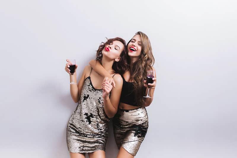 stilvolle Freunde posieren mit Gläsern Wein