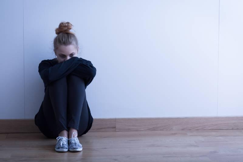 traurige Frau, die zu Hause auf dem Boden sitzt