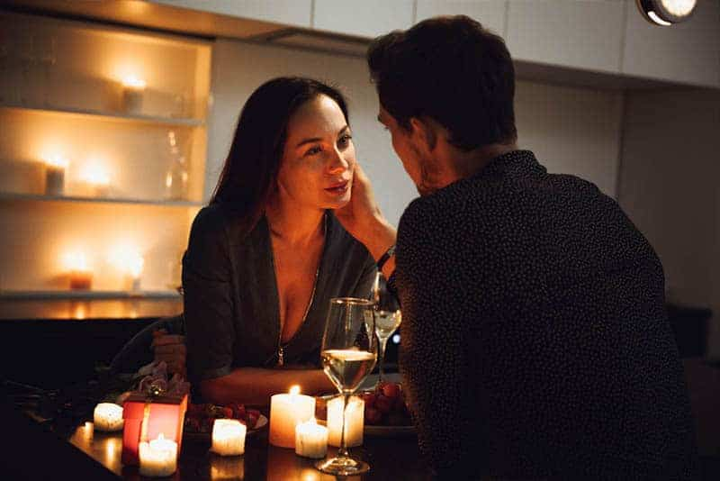 verliebte Frau, die Mann am Datum Abendessen betrachtet