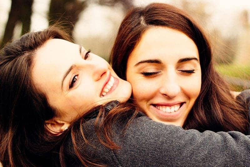 zwei junge Frauen umarmen sich fest