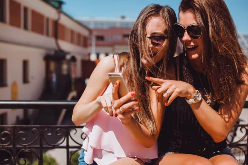 zwei lächelnde Freunde, die etwas auf ihrem Handy beobachten