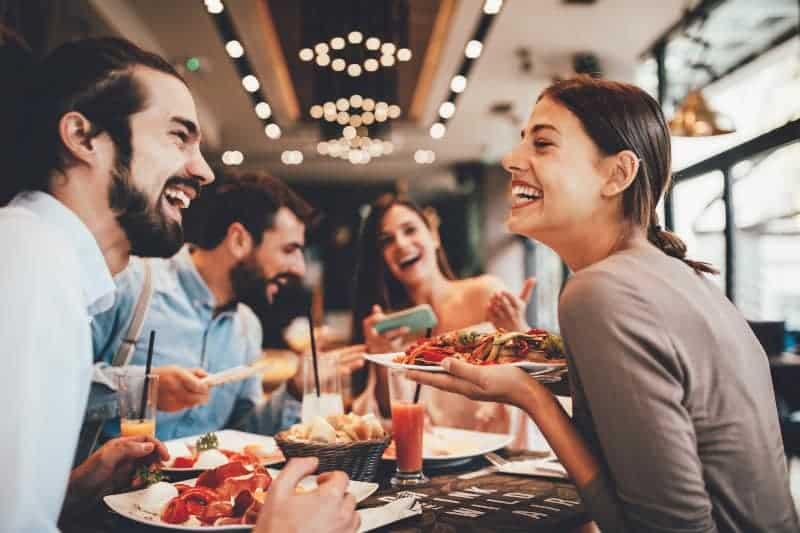 zwei lächelnde Paare, die sich zum Abendessen in ein Restaurant setzen