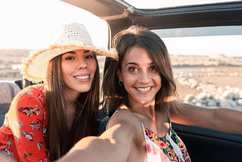 zwei schöne Frauen, die in einem Auto fahren