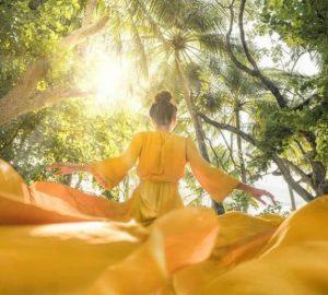 Ein Mädchen in einem gelben Kleid tanzt in der Natur