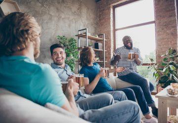 lächelnde Freunde sitzen und trinken Bier und reden
