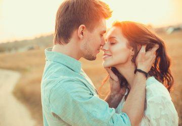 Ein junges Liebespaar umarmt und küsst sich draußen