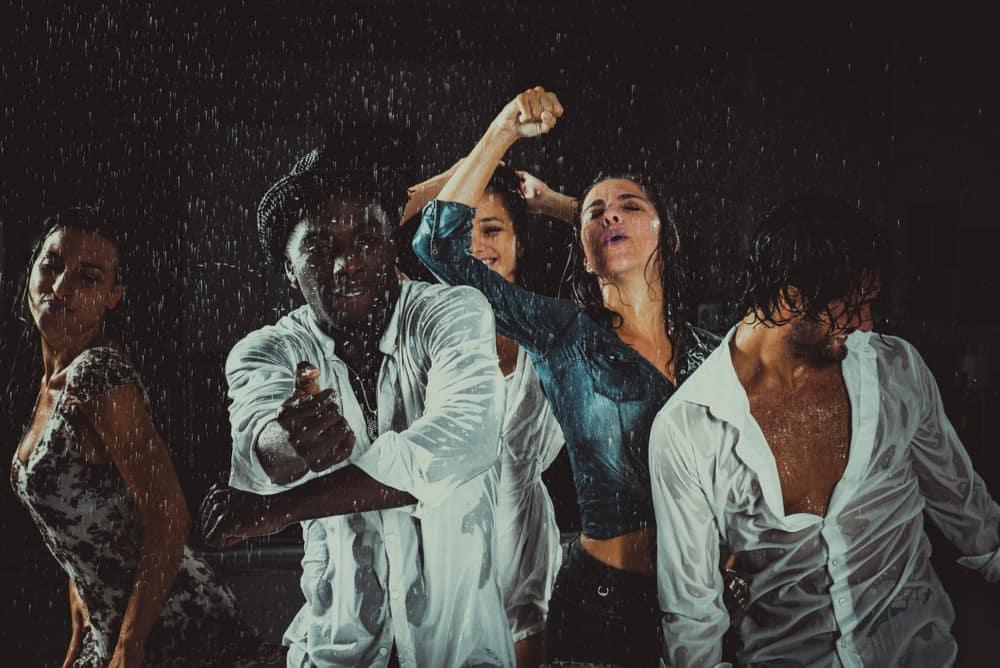 Abends tanzt eine Gruppe von Freunden im Regen