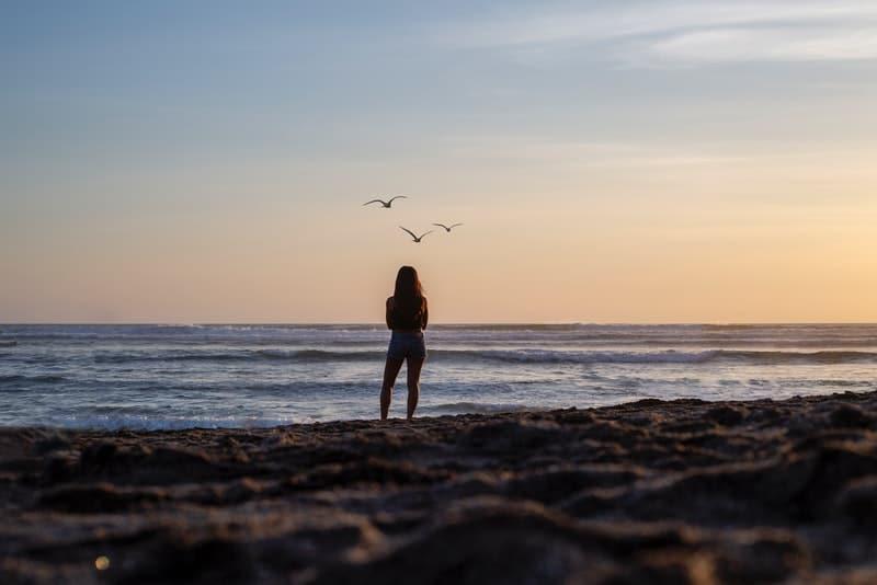 Am Strand am Meer steht eine Frau in kurzen Hosen