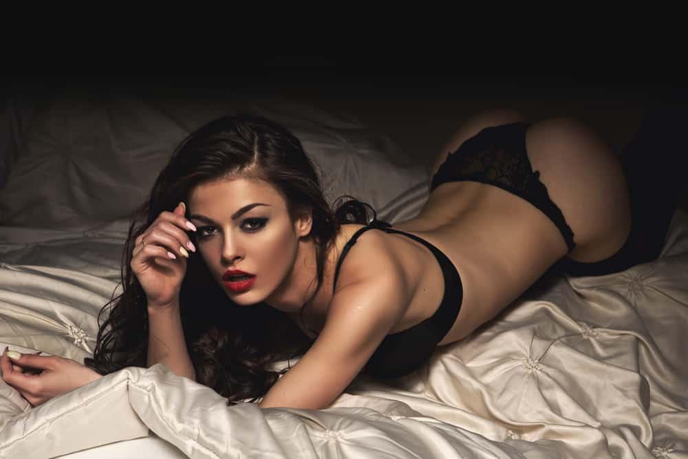 Auf dem Bett liegt eine hübsche Brünette in sexy Dessous