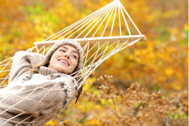 Auf der Hängematte liegt eine lächelnde Frau in einem Pullover und einer Wintermütze