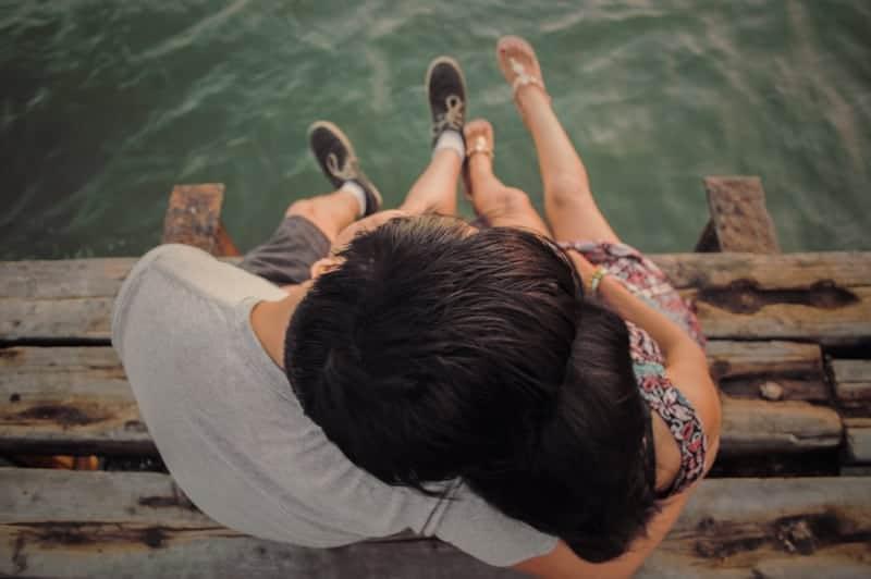 Auf einer alten Holzbrücke über den Fluss sitzt ein umarmendes Liebespaar