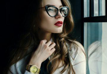 attraktive Brünette mit rotem Lippenstift und Brille am Fenster