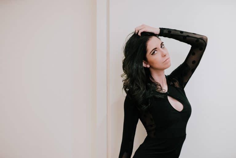 Das Mädchen im schwarzen Body posiert