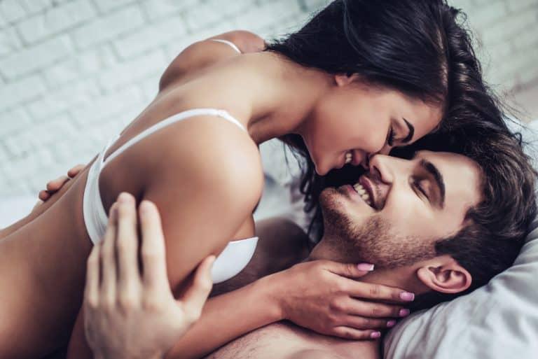 Das Mädchen liegt über dem Jungen im Bett
